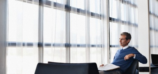 Middle-aged business man sitting in office chair and looking through window