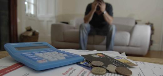 man holds head in hands, credit cards bills money for debt