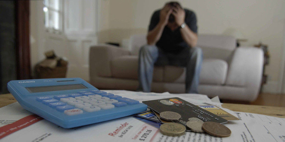 man holds head in hands, credit cards bills money for debt
