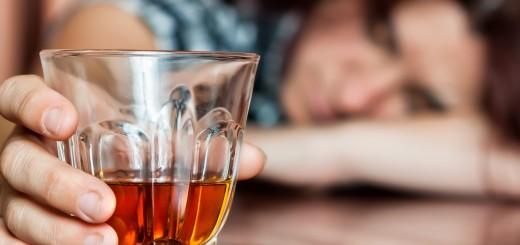 Asleep drunk woman holding an alcoholic drink