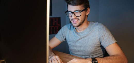 Happy man in glasses typing on computer at home