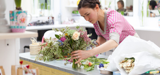 Smiling florist at work with bunch of flowers